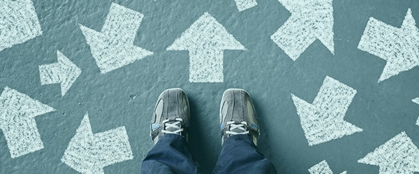 Person standing in behind arrows on pavement representing the Buyers Journey and Sales Process